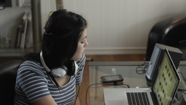 vídeos de stock, filmes e b-roll de ms teenage girl (16-17) using laptop and mobile phone at home / orem, utah, usa - orem