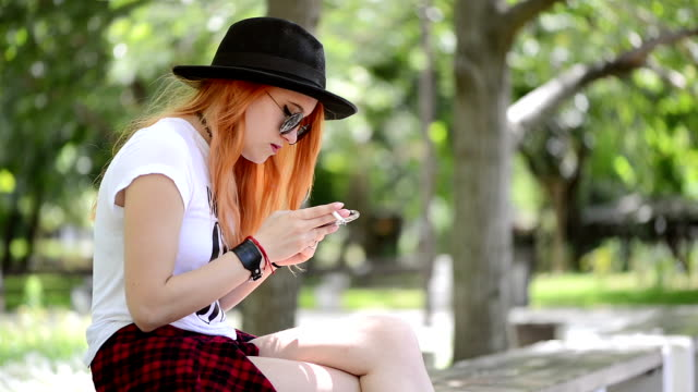 teenage girl using smartphone in city and smoking a cigarette - sigaretta video stock e b–roll