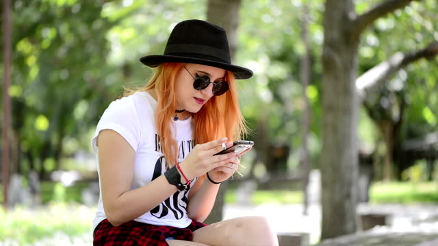 Teenage girl using smartphone in city and smoking a cigarette