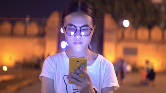 teenage girl using smartphone in the capital city with tha pae gate local famous place in background - anamorphic stock videos & royalty-free footage