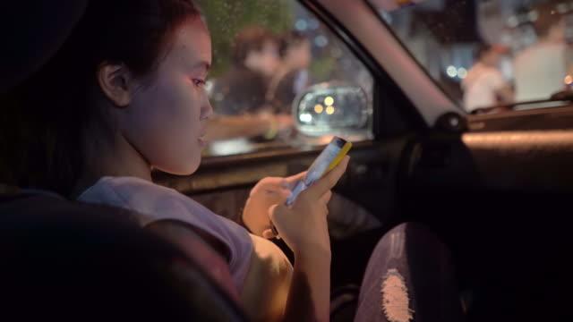 vídeos de stock, filmes e b-roll de adolescente usando smartphone no carro com carro de trânsito em segundo plano - só uma adolescente menina