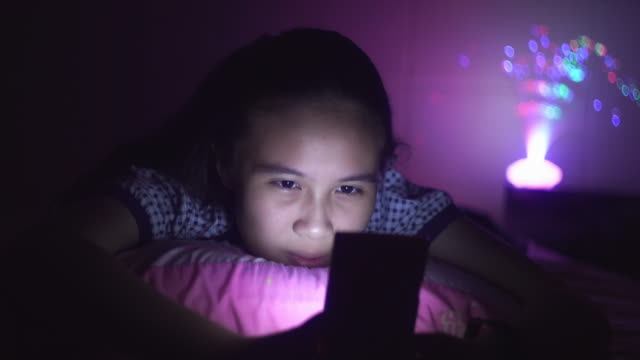 teenage girl using smartphone on the bed - beautiful people stock videos & royalty-free footage