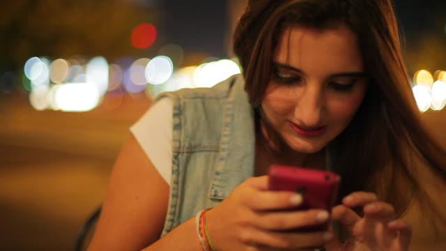 vídeos y material grabado en eventos de stock de teenage girl using smartphone outdoors at night - sólo una adolescente