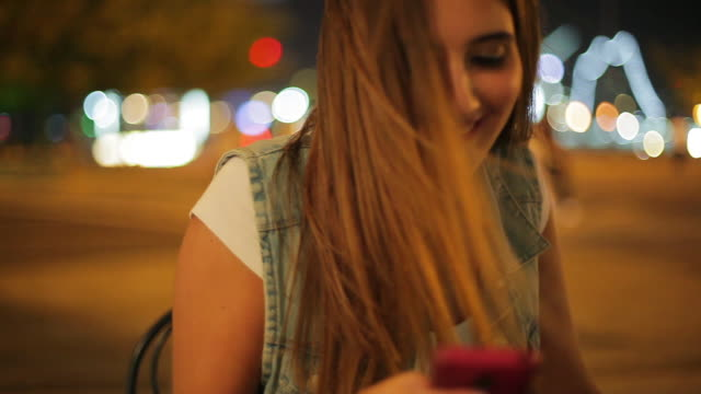 teenage girl using smartphone to text message outdoors at night - one teenage girl only stock-videos und b-roll-filmmaterial