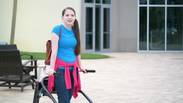stockvideo's en b-roll-footage met tiener die wandelaar gebruikt die zich buiten hoge school bevindt - 14 15 years