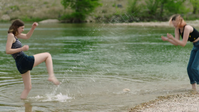 teenage girl wading in river kicks water up and splashes sister on rocky shore. - mischief stock-videos und b-roll-filmmaterial