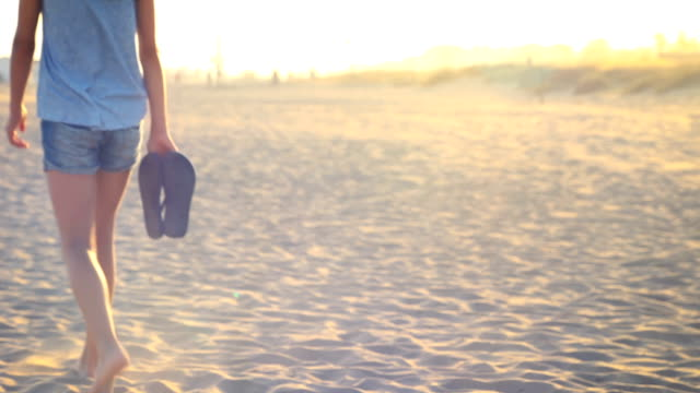 vídeos y material grabado en eventos de stock de teenage girl walking on the sand at the beach. beautiful natural sun flare. - sandalia