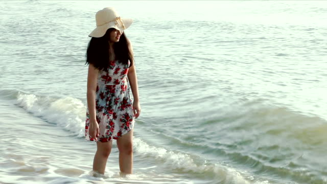 teenage girl walking on the sandy beach next to the water edge, - wet stock videos and b-roll footage