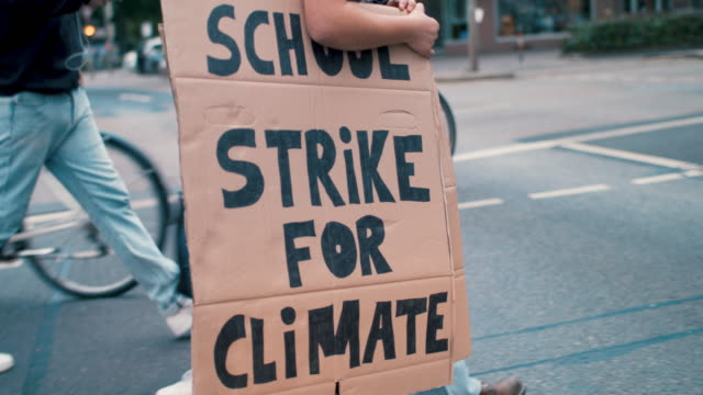 teenage girl walking street holding climate school strike protest sign - climate stock videos & royalty-free footage
