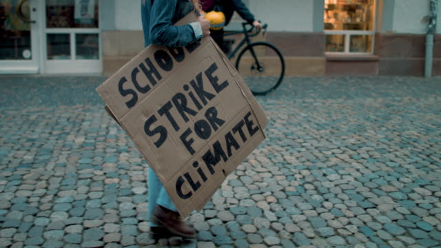 Teenage girl walking street holding climate school strike protest sign