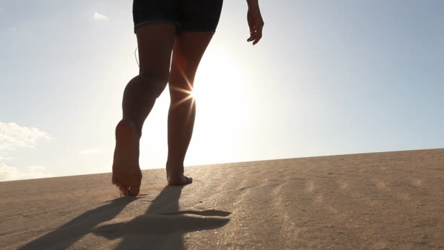 teenage girl walks into sand dunes, riases arms to sun - one teenage girl only stock videos & royalty-free footage