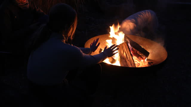 teenage girl warming hands over fire pit - one teenage girl only stock videos & royalty-free footage