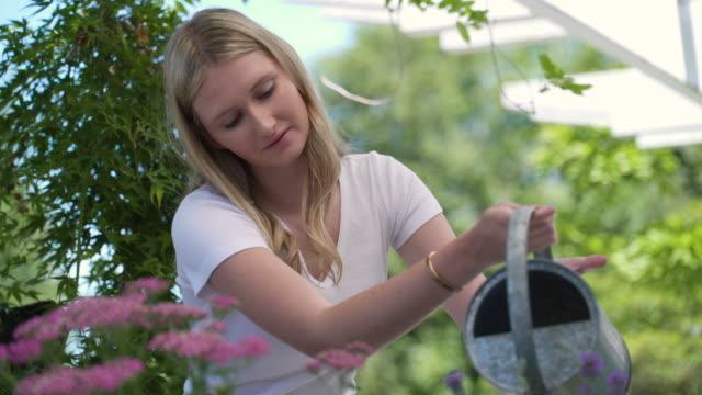 teenage girl watering flowers - one teenage girl only stock videos & royalty-free footage