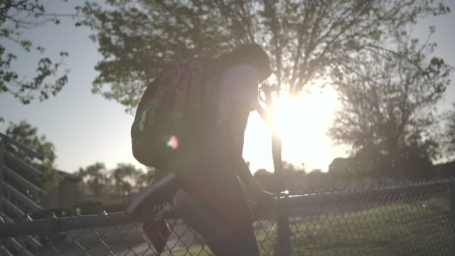 vídeos de stock, filmes e b-roll de ws teenage girl wearing a backpack climbing over a fence - cerca