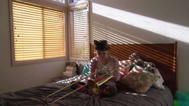 WS Teenage girl wearing cat ears and playing trombone in her bedroom