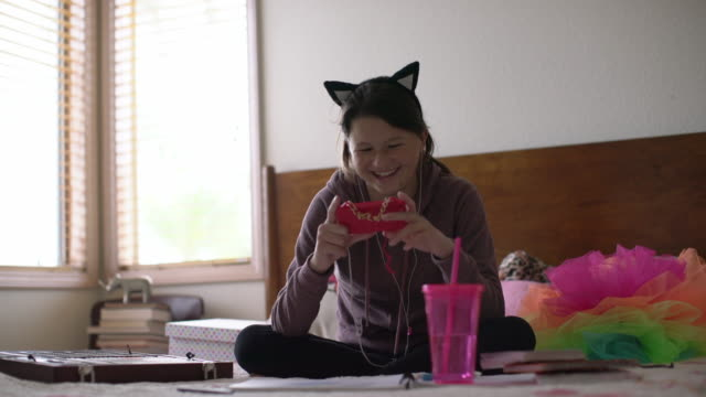 ms teenage girl wearing cat ears texting on her phone in her bedroom - hair accessory stock videos and b-roll footage