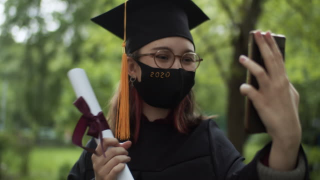 vídeos de stock e filmes b-roll de teenage girl wearing graduation gown and cap and protective mask greeting a relative or friend on video call or making selfie at smartphone - boné