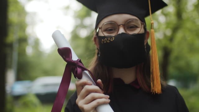 teenage girl wearing graduation gown and cap and protective mask - female high school student stock videos & royalty-free footage