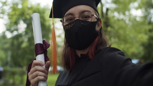 stockvideo's en b-roll-footage met tiener die graduatiejurk en glb en beschermend masker draagt - slagen school