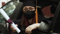 Teenage girl wearing graduation gown and cap and protective mask with diploma in car