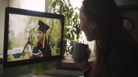 tonårsflicka bär examen klänning och mössa hälsning hennes släkting eller vän på videosamtal - examen bildbanksvideor och videomaterial från bakom kulisserna