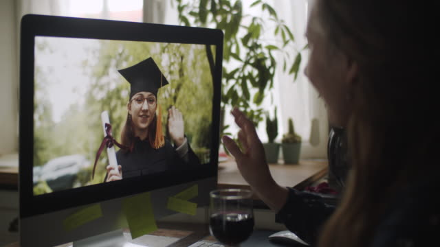 teenage girl wearing graduation gown and cap greeting her relative or friend on video call - cap stock videos & royalty-free footage