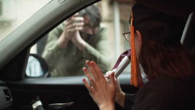 teenage girl wearing graduation gown and cap with diploma in car and a men greeting her from a street - graduation stock videos & royalty-free footage