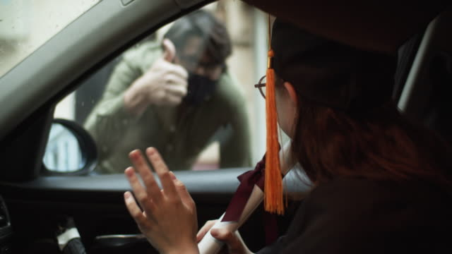 teenage girl wearing graduation gown and cap with diploma in car and a men greeting her from a street - diploma video stock e b–roll
