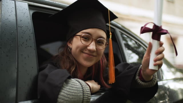 teenage girl wearing graduation gown and cap with diploma in car - diploma stock videos & royalty-free footage
