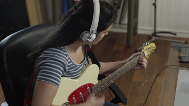 ms ds teenage girl (16-17) wearing headphones playing electric guitar in home / orem, utah, usa - エレキギター点の映像素材/bロール