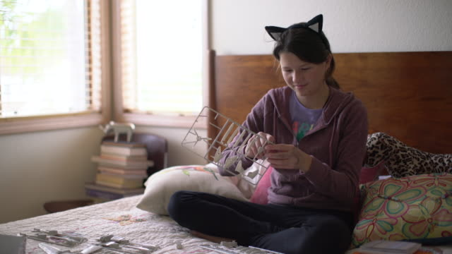 MS Teenage girl wearing kitty ears putting together a model in her bedroom