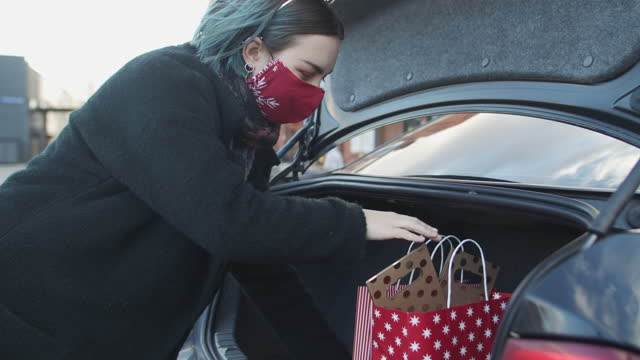 teenage girl wearing protective face mask putting gifts in car after christmas shopping during covid-19 pandemic - bag stock videos & royalty-free footage