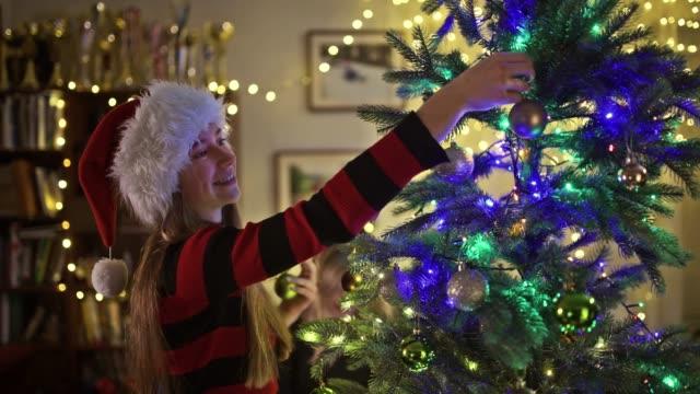 teenage girl wearing santa hat decorating the christmas tree - santa hat stock videos & royalty-free footage