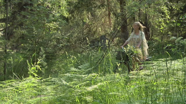 slo mo ws pan teenage girl (14-15) wearing sundress cycling in forest / gavle, gavleborg county, sweden - sundress stock videos & royalty-free footage