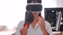 Teenage girl wearing virtual reality headset and gesturing while while sitting at her desk in desk and working hackathon in workshop.Innovation,Education,Technology,Science,People concept.Education Topics.Industry 4.0.Women in STEM