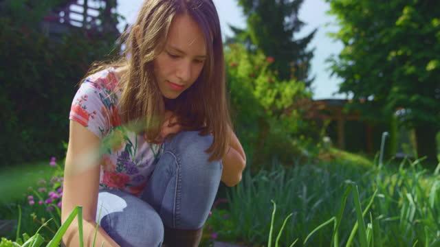 slo mo tu 10代の少女は晴れた日に庭のベッドを雑草 - one teenage girl only点の映像素材/bロール
