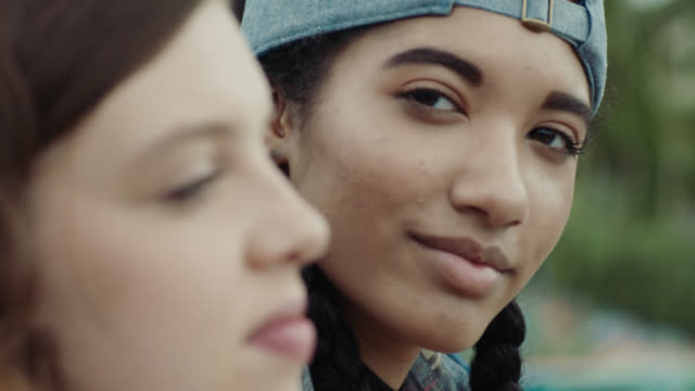 Teenage Girl With Backwards Cap Turns And Looks At Camera
