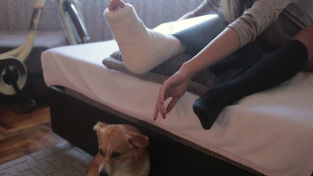 vidéos et rushes de adolescente avec la jambe cassée câlinant son crabot à la maison - accident domestique