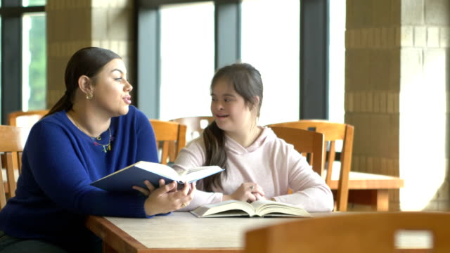 teenage girl with down syndrome and friend studying - persons with disabilities stock videos & royalty-free footage