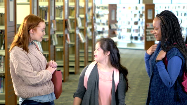 teenage girl with down syndrome and friends in library - learning disability stock videos & royalty-free footage