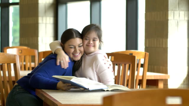 teenage girl with down syndrome, friend study and hug - 16 17 years stock videos & royalty-free footage