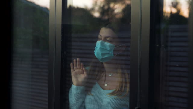 teenage girl with face mask looking through window - teenagers only stock videos & royalty-free footage