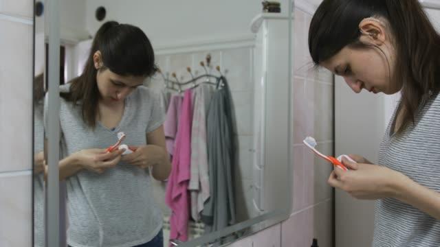 vídeos y material grabado en eventos de stock de chica adolescente con audífono en casa - sordera
