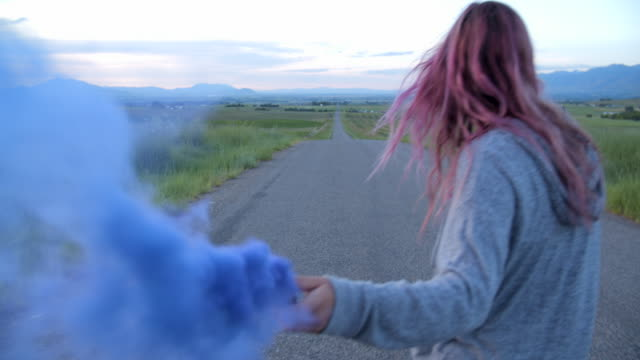 vídeos de stock e filmes b-roll de ms teenage girl with pink hair playing with blue smoke while skateboarding - colorido