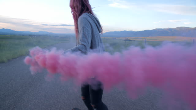 stockvideo's en b-roll-footage met ms teenage girl with pink hair playing with pink smoke while skateboarding - dag