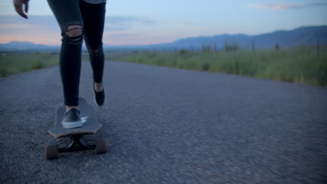 cu teenage girl with pink hair skateboarding down a road - pink hair stock videos & royalty-free footage