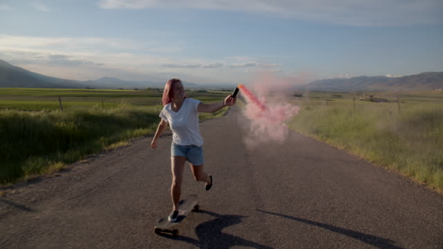 ws teenage girl with pink hair skateboarding down a road - pink hair stock videos & royalty-free footage