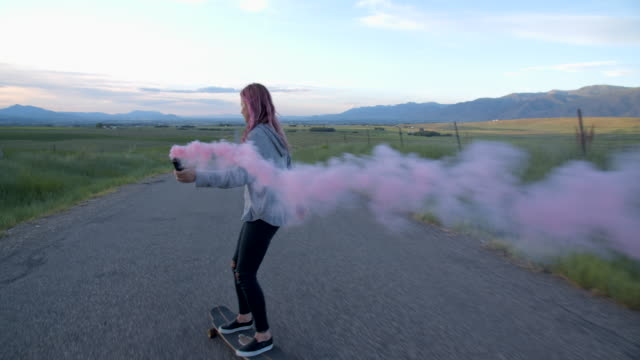 ws sm teenage girl with pink hair skateboarding down a road - pink hair stock videos & royalty-free footage