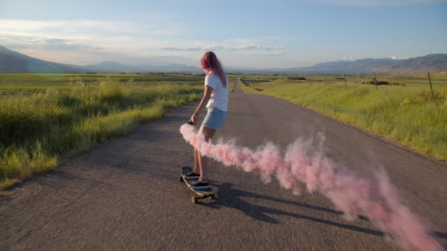 ws teenage girl with pink hair skateboarding down a road - shorts stock-videos und b-roll-filmmaterial