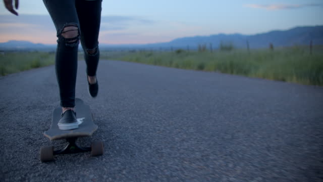 sm cu teenage girl with pink hair skateboarding down a road - pink hair stock videos & royalty-free footage